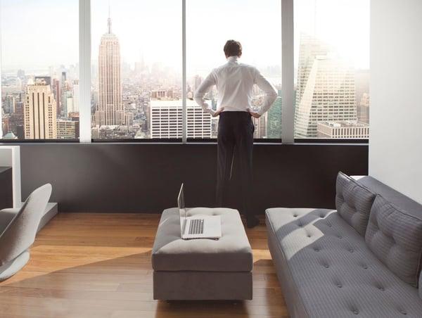 een jongeman in zijn luxe appartement met uitzicht op de Skyline van New York...