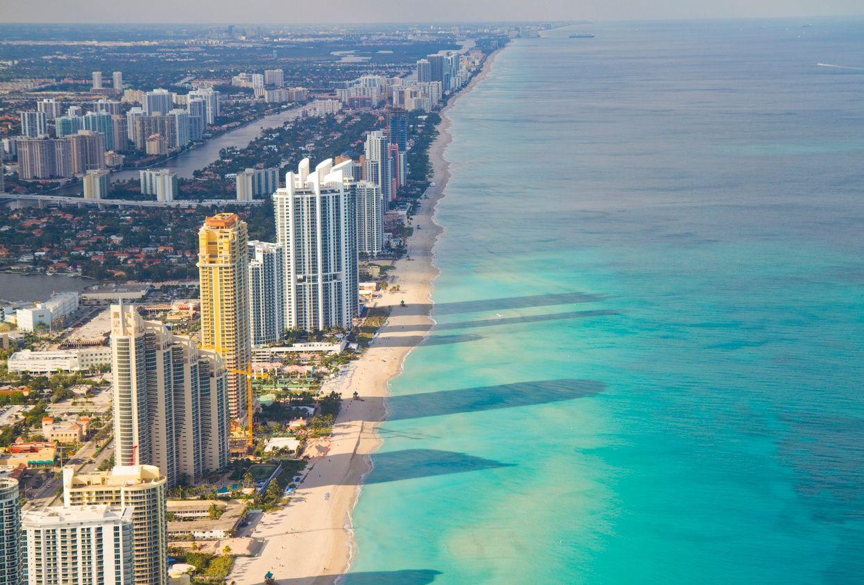 een bovenaanzicht van hoge flatgebouwen langs Miami Beach