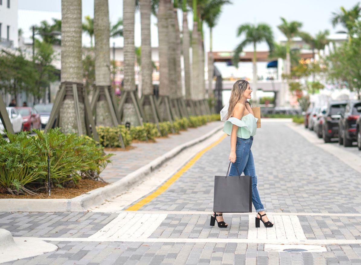 vrouw die een boodschappentas vasthoudt en de straat oversteekt in Coral Gables...